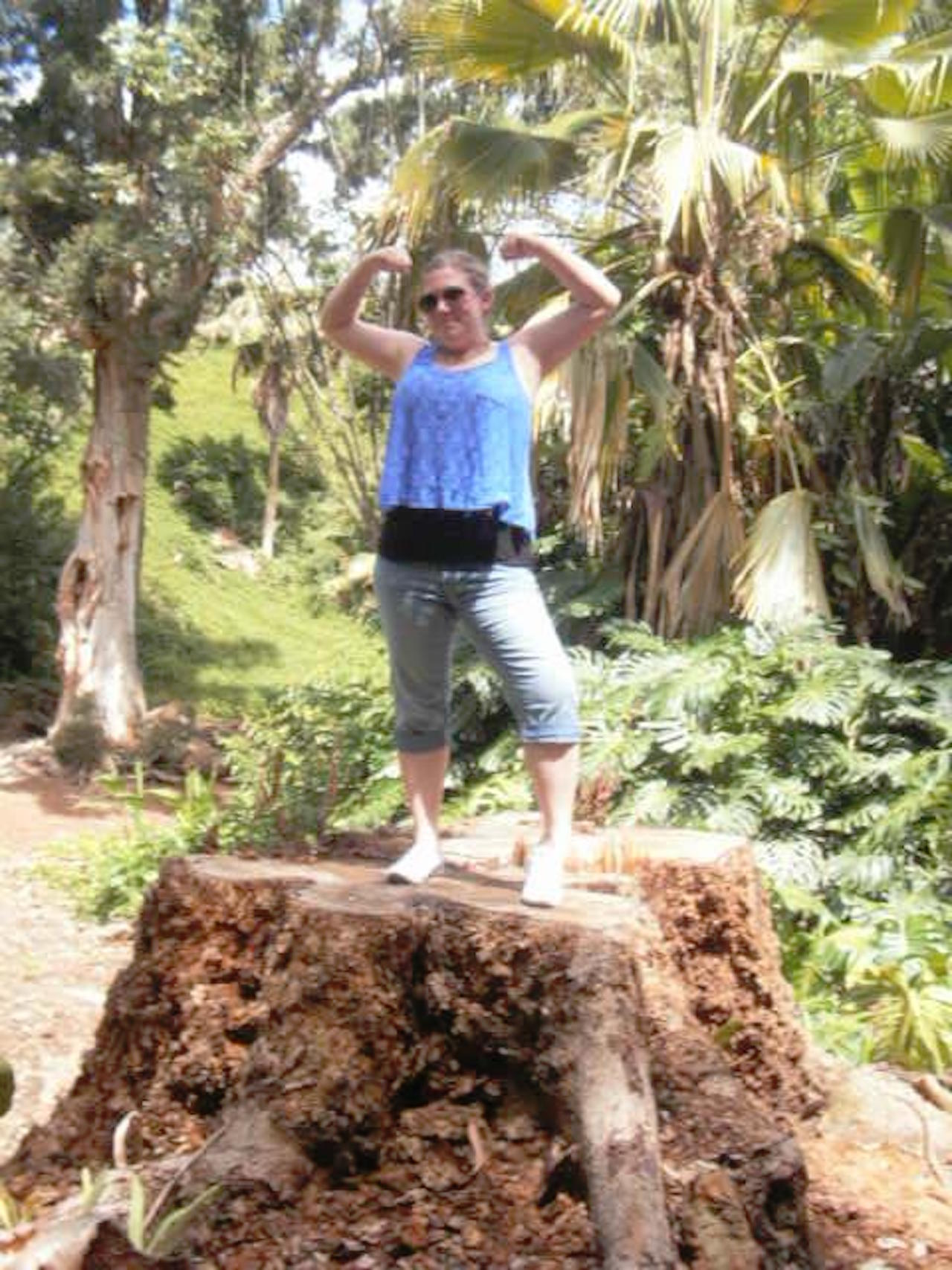 woman flexing her muscles standing on a rock