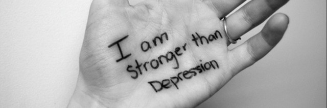 "A hand with the words ""I am stronger than depression,"" on the palm."