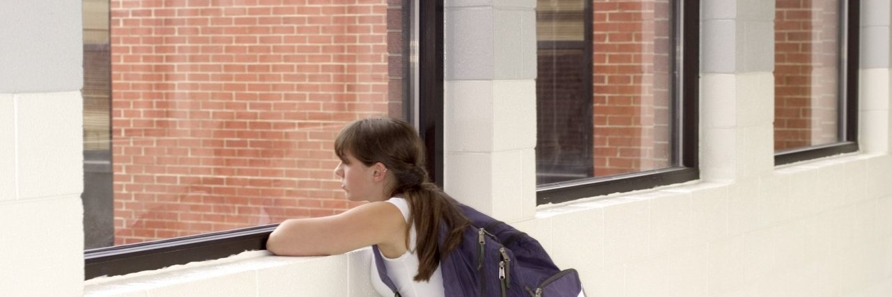 Teenage girl looking out window