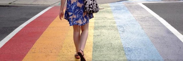 Woman walking on a sidewalk with a painted rainbow on the ground.