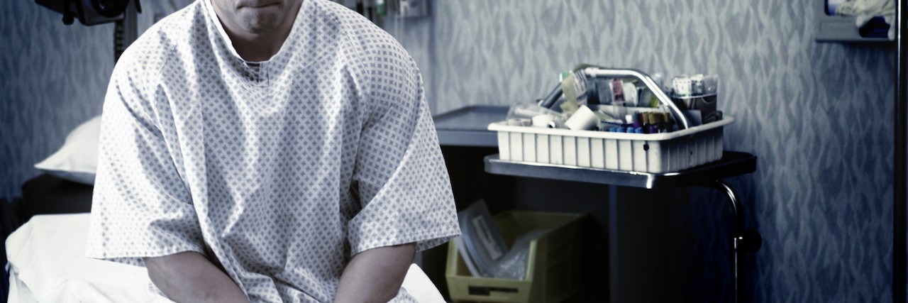 Sad man sits on edge of hospital bed in hospital gown