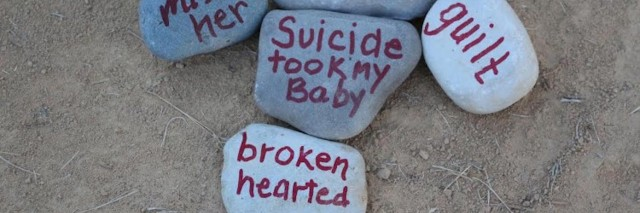 Rocks with words written on them in red marker: miss her, depression, guilt, suicide took my baby and broken hearted
