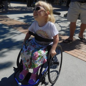 Heidi, a little girl with spinal muscular atrophy pushing her wheelchair.
