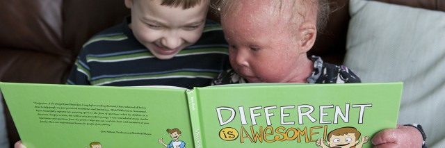 Two children, one with icthyosis, reading a book titled 'Different is Awesome.'