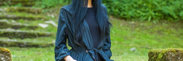 Woman sitting in black coat on staris in a grassy landscape