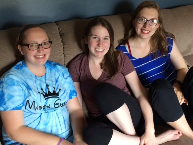three women sitting on a couch together