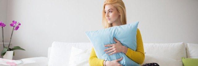A young woman holds her pillow as she sitts on a bed