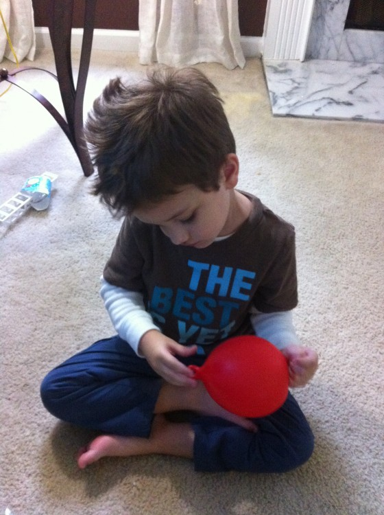 young boy playing with a red balloon