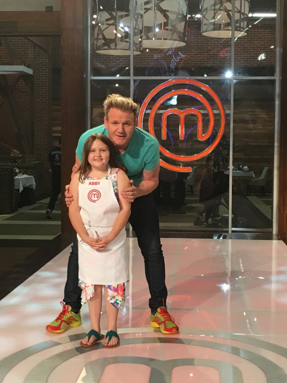 Gordon Ramsay standing behind Abby on the set.