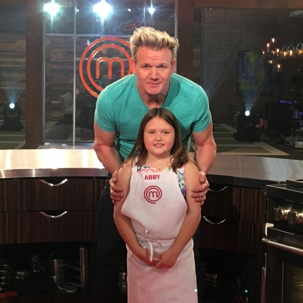 Gordon Ramsay standing behind Abby on the show's set.