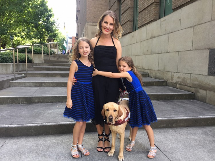 woman and two girls stand on steps with guide dog