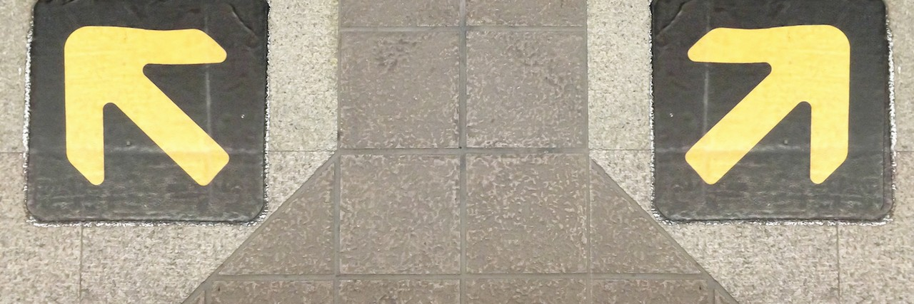 Two feet on a sidewalk with two opposite-facing arrows painted on it