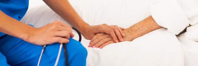 Nurse with stethoscope is show embracing the hand of a patient as they sit on the patient's bed