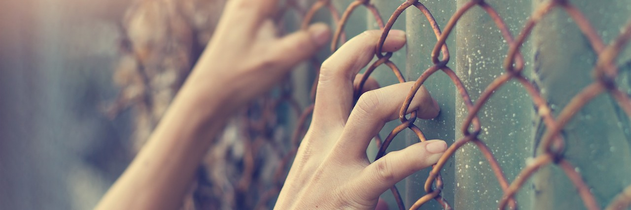 Hands clinging to a gate