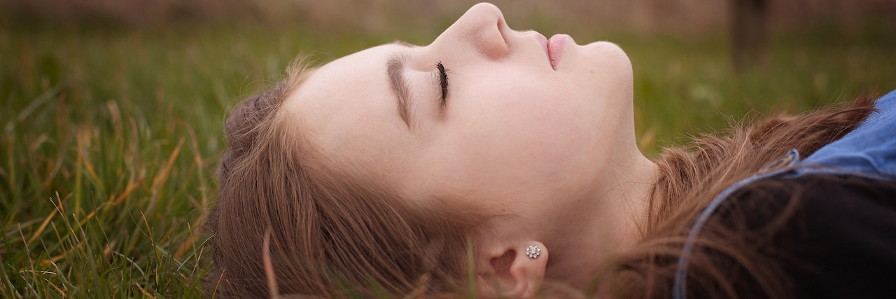 Up close, side shot of a young girl laying in the grass with her eyes closed