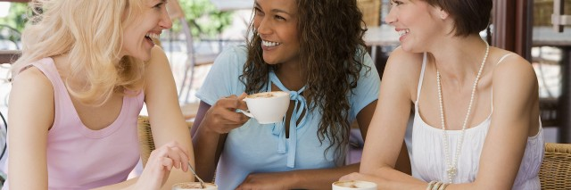 Three adult women smiling and talking over coffee