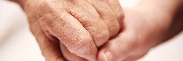 Close up shot of two hands embracing, one person reassuring the other person