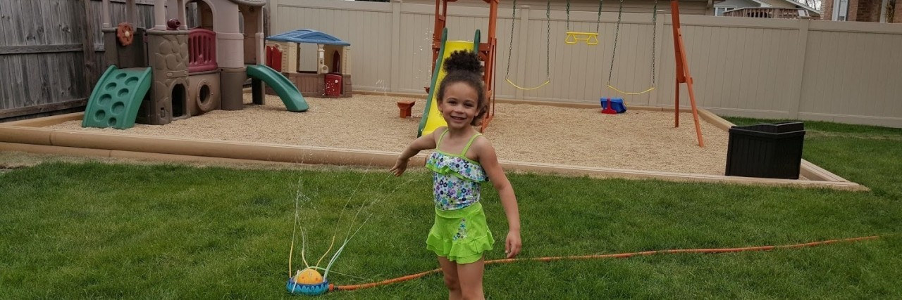 Heather's daughter Maya playing in the sprinkler