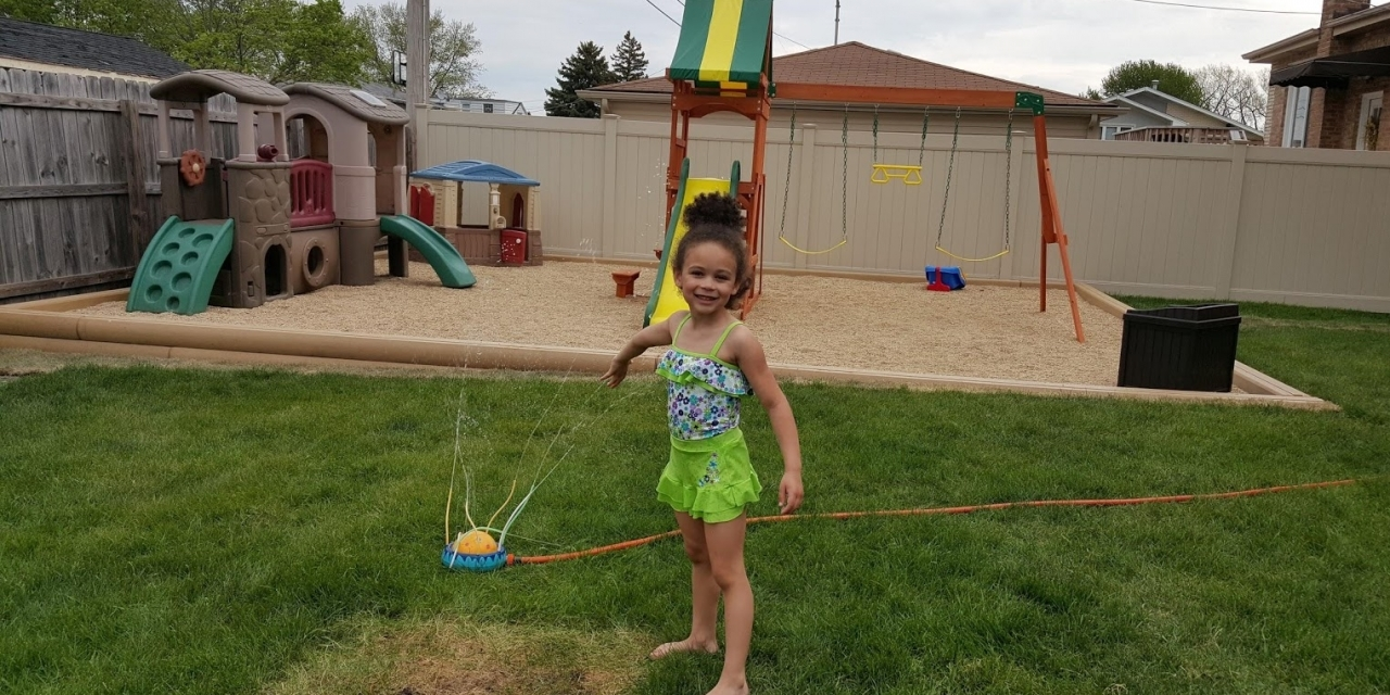 Heather's daughter Maya playing in the sprinkler