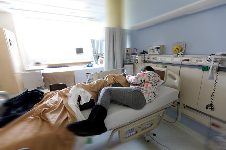Lauren lying in bed next to her son.