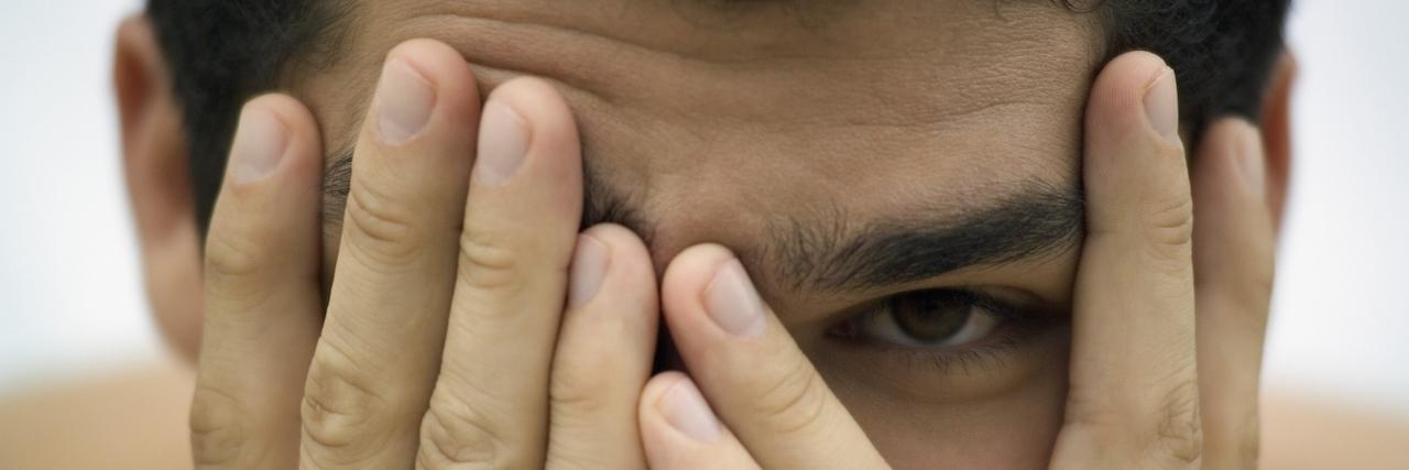 Man hides face between hands