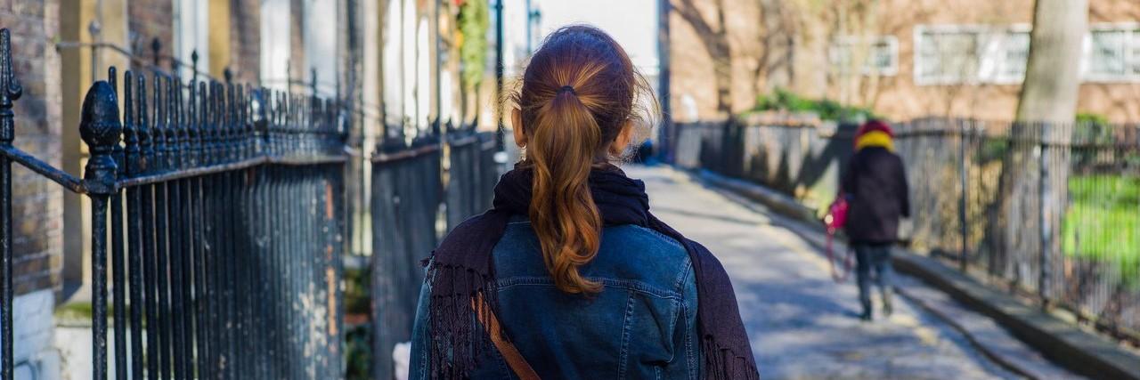 Woman walking cobbled street
