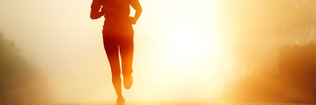 Woman running with sunrise behind her