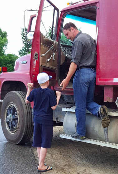 A man standing near the door of a red construction truck, holding his hand out to the author's son