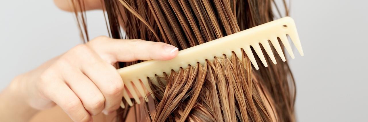 girl running a comb through her wet hair