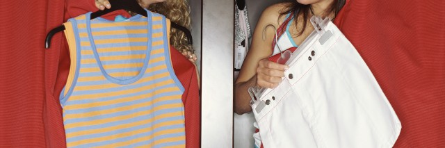 Two girls poke their heads out of their dressing rooms to show each other clothes