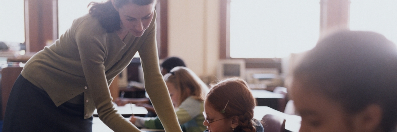 Teacher leans over student's desk, helping with assignment