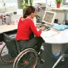 Woman in wheelchair at computer.