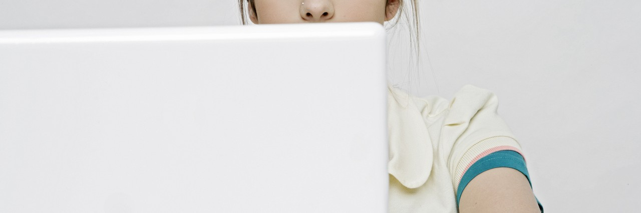 View of a teenage girl working with a laptop.