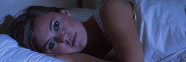 woman lying in bed who can't sleep