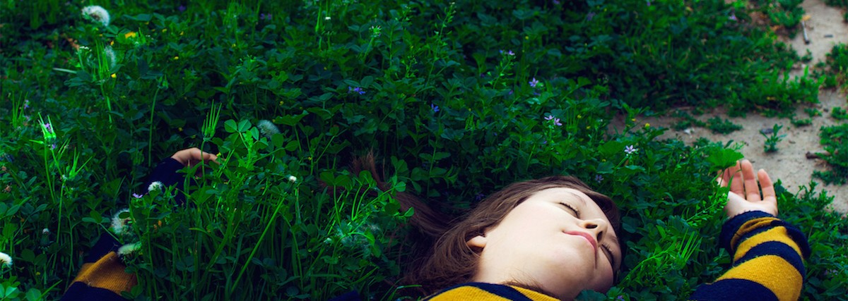 A girl rests unconscious in a beautiful field of green.