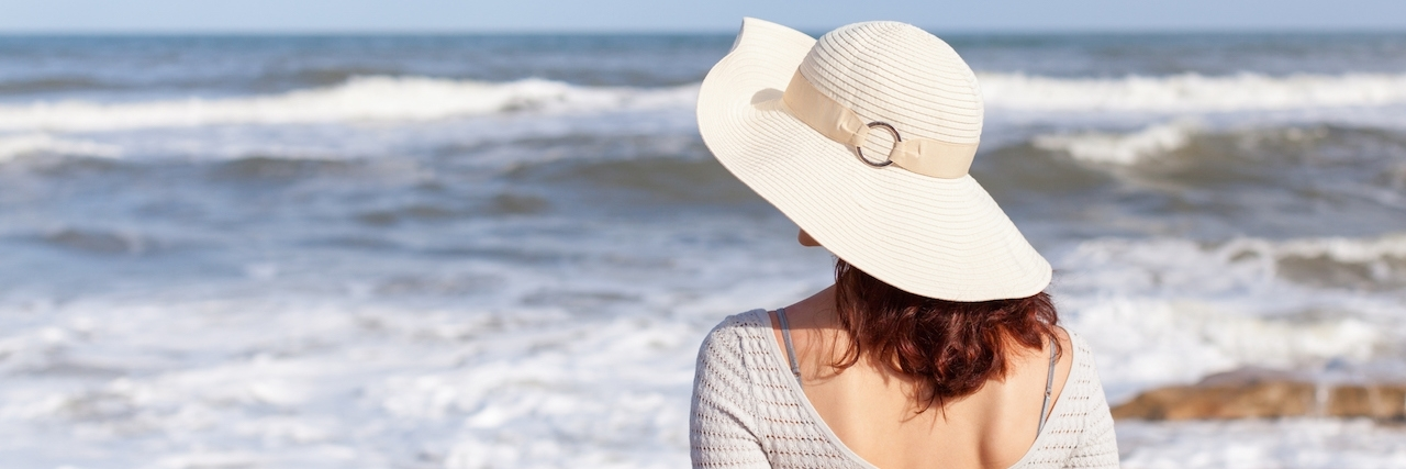 A young woman in a white hat looking away from the camera, watching waves.