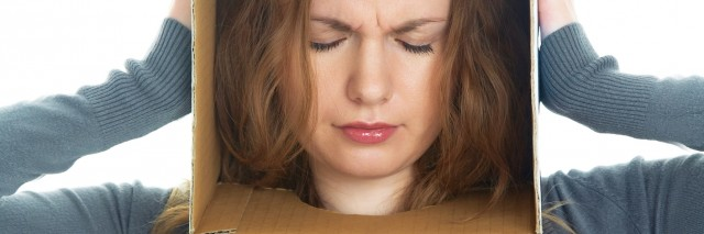 conceptual portrait of a woman's head hidden in a cardboard box