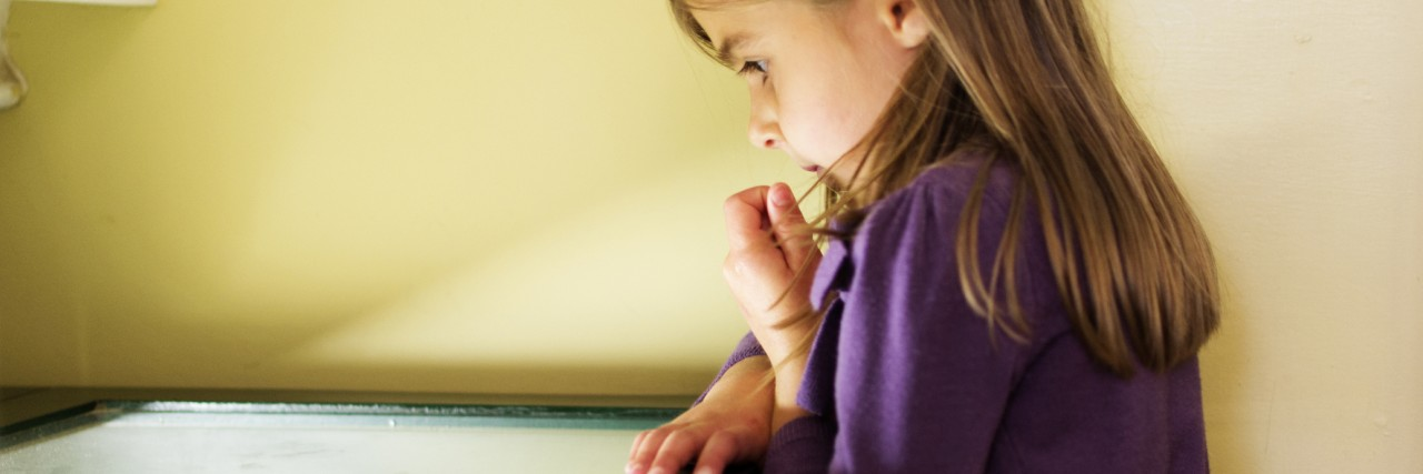 A young girl peers into the lit display cabinet in a museum