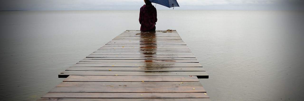 A man holdning an umbrella, sitting at the end of a dock