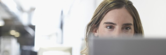 businesswoman looking at a laptop in an office