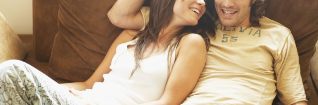 Young couple sitting together on a couch and smiling