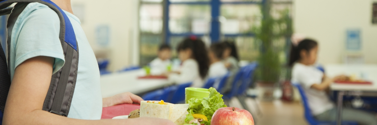 Girl holding food tray in school cafeteria.