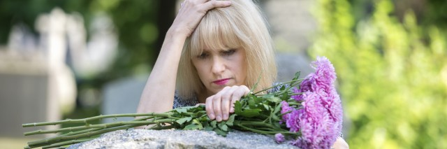 Woman mourns with her hand on headstone in cemetery in closeup