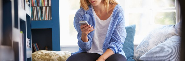 Woman Sitting On Couch At Home Using Mobile Phone