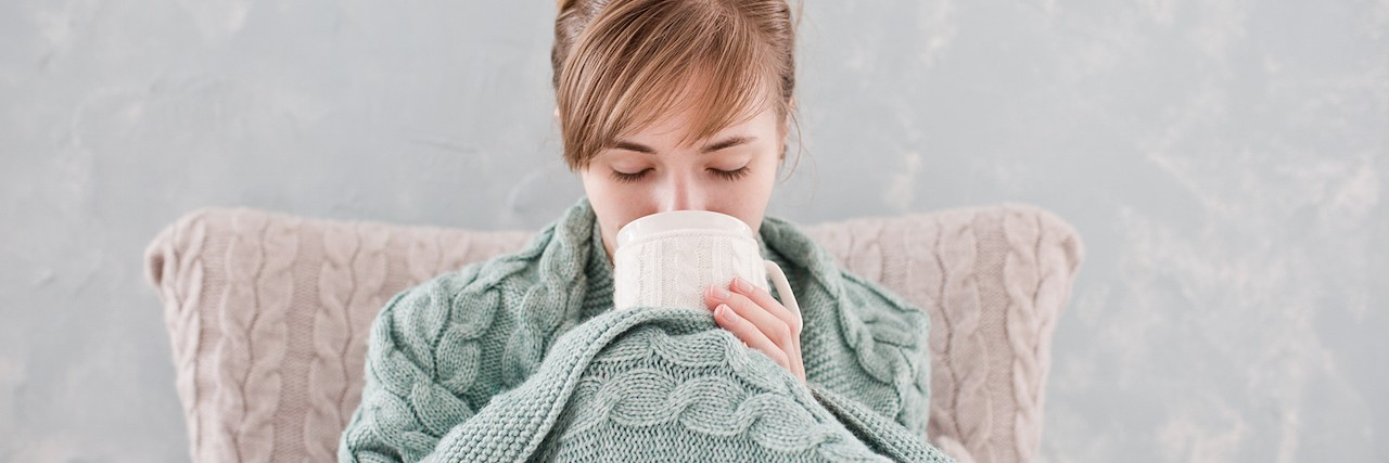 woman with cup of tea, sitting wrapped in a blanket