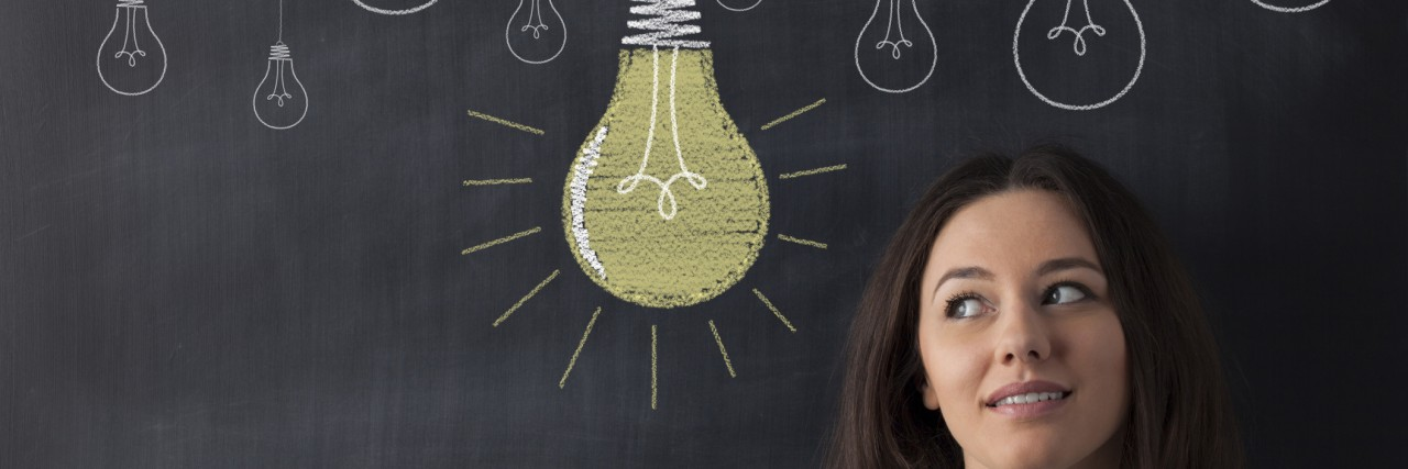 Young business woman standing with her back against a blackboard. She is looking to a big glowing light bulb.