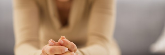 Close-up of woman's hands clasped together on table