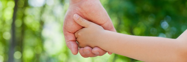 Parent holds the hand of a little child.