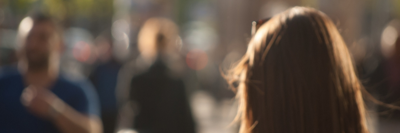 People walking down the street in the evening, beautiful light at sunset. The photo is purposely made out of focus, no faces are recognisible