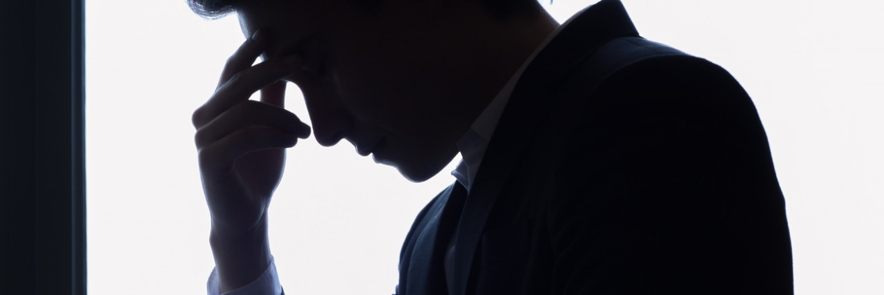 Silhouette of stressed man wearing a suit
